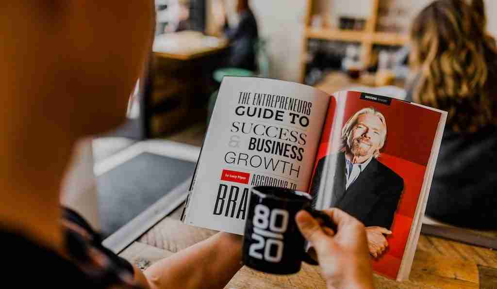 "Man reading a financial education magazine. The page has a picture of Richard Branson (right side) and the title ""The entrepreneurs guide to success & business growth"""